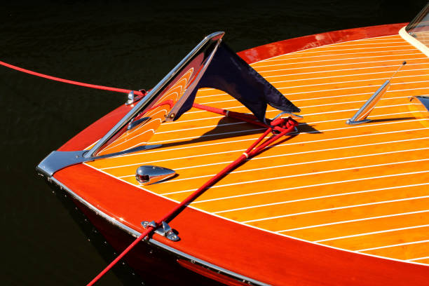 bow of vintage wooden boat with crome reflecting wood stripes - red and yellow - vintage nautical stock photos and pictures