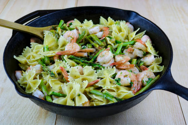 Bow Tie Pasta Freshly made bowtie pasta with asparagus and shrimp in a cast iron pan bow tie pasta stock pictures, royalty-free photos & images