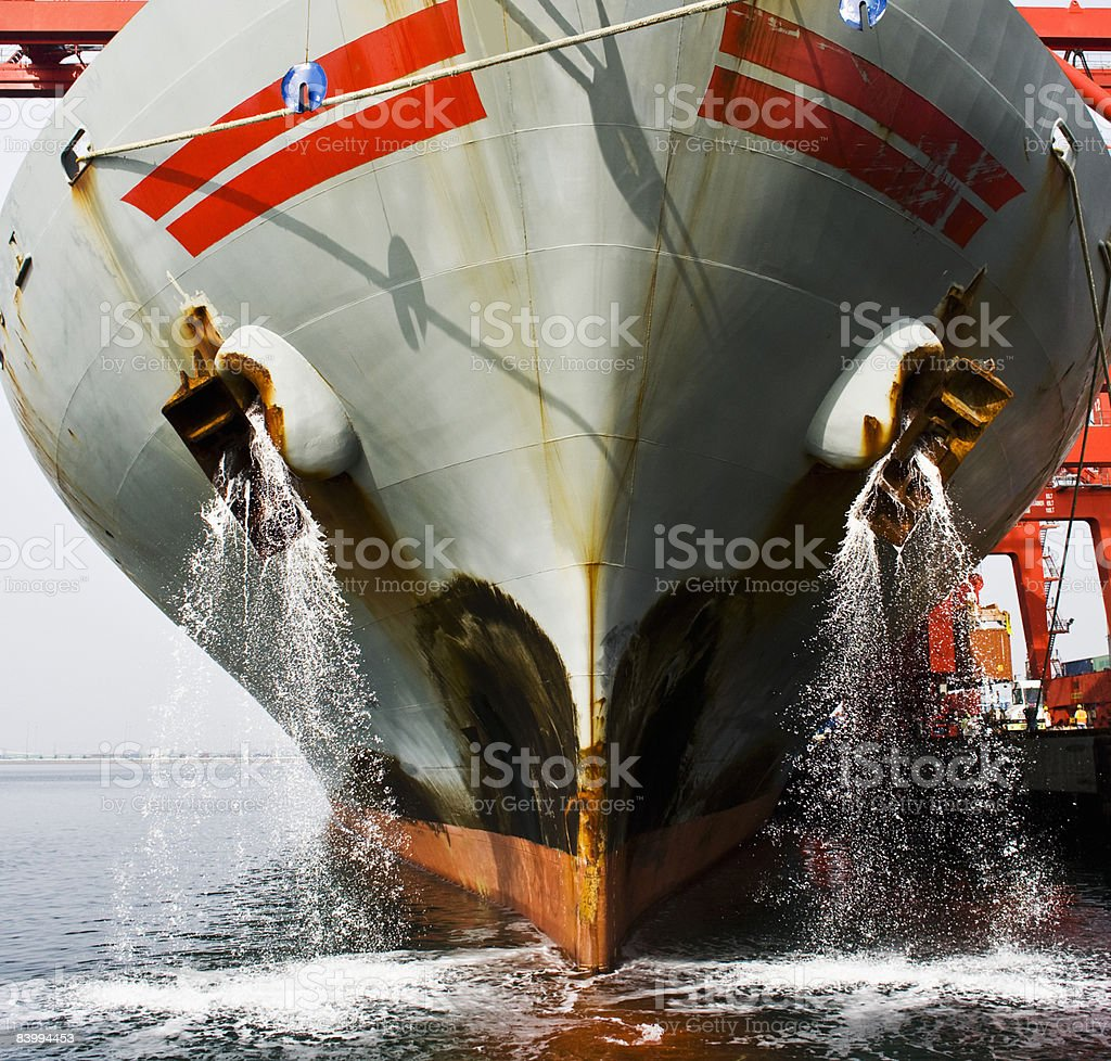 Bow view of docked cargo ship deck being flushed. royalty-free stock photo