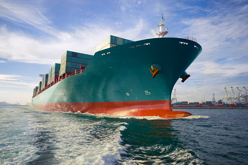 Bow View Of Loaded Cargo Ship Sailing Out Of Port Stock Photo - Download Image Now