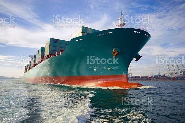 Bow view of loaded cargo ship sailing out of port.  California Stock Photo
