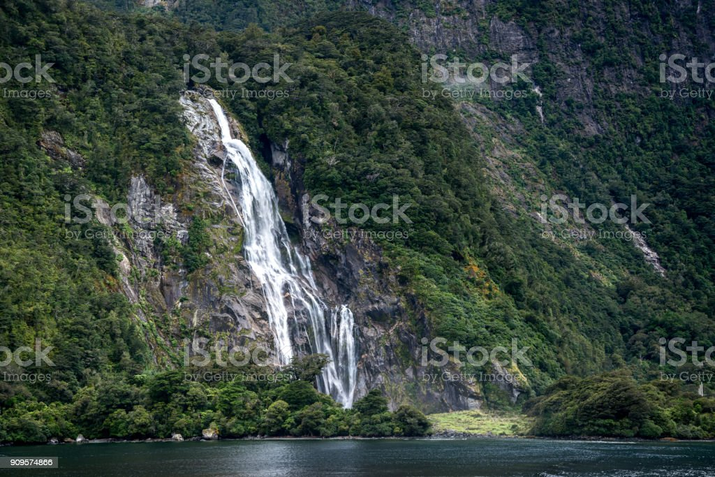 Bowen waterfalls in the mountain and forest at Milford Sound, New Zealand stock photo