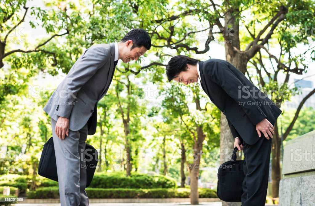 Bowing - two Japanese businessmen greeting each other in Tokyo stock photo