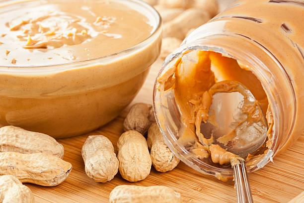 bowl and jar of creamy peanut butter among scattered peanuts - peanutbutter bildbanksfoton och bilder