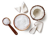 Wooden bowl and spoon of coconut oil and fresh coconut pieces isolated on white background