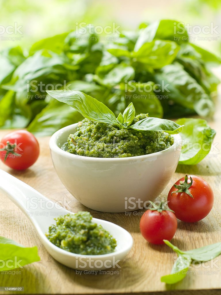 Bowl and spoon of green pesto over greens and tomatoes stock photo