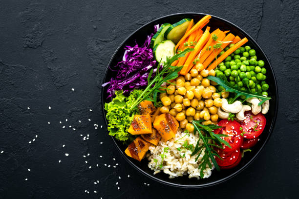 plato tazón con arroz, pepino, tomate, guisantes, lombarda, garbanzos, ensalada de lechugas frescas y las nueces de acajú. saludable balanceada comer - vegana fotografías e imágenes de stock