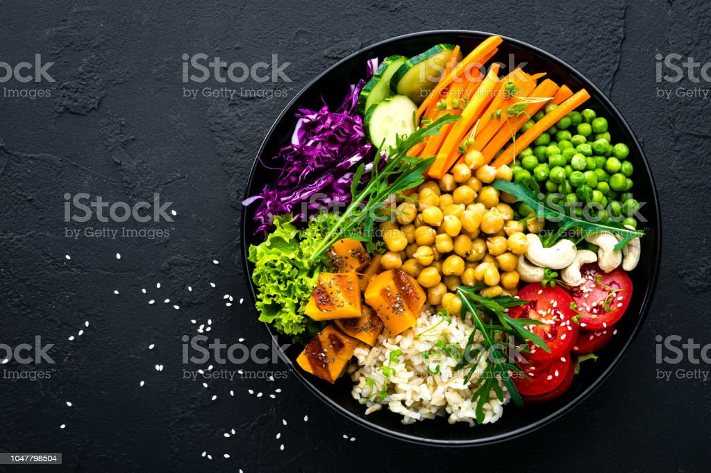 Bowl dish with brown rice, cucumber, tomato, green peas, red cabbage, chickpea, fresh lettuce salad and cashew nuts. Healthy balanced eating stock photo