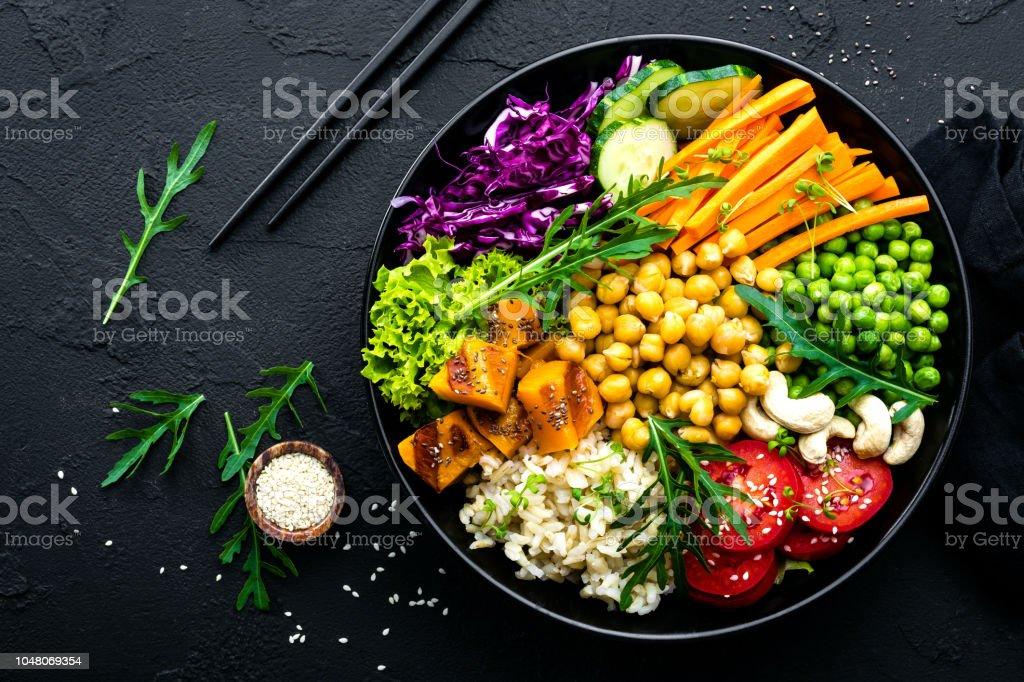 ボウル皿玄米、キュウリ、トマト、グリーン ピース、赤キャベツ、ひよこ豆、新鮮なレタスのサラダとカシュー ナッツ。正常なバランスのとれた食事 ストックフォト