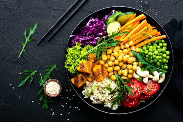 ボウル皿玄米、キュウリ、トマト、グリーン ピース、赤キャベツ、ひよこ豆、新鮮なレタスのサラダとカシュー ナッツ。正常なバランスのとれた食事 - ローフード ストックフォトと画像