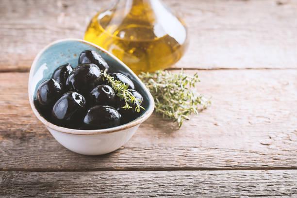 tazón de fuente lleno de aceitunas negras frescas - negras maduras fotografías e imágenes de stock