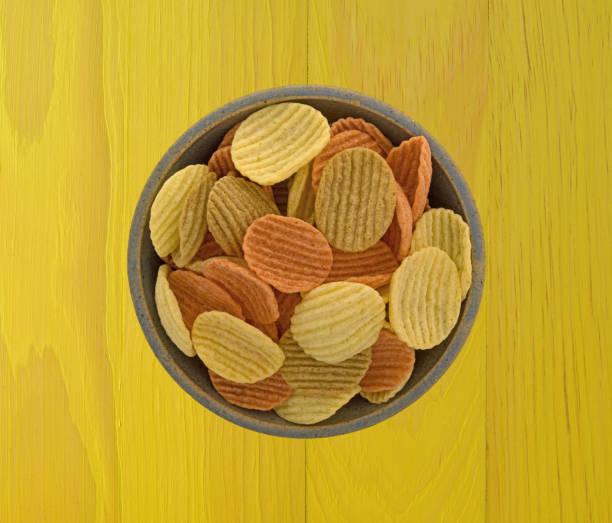 schüssel gefüllt mit gemüse chips auf einem holztisch - gemüsechips stock-fotos und bilder
