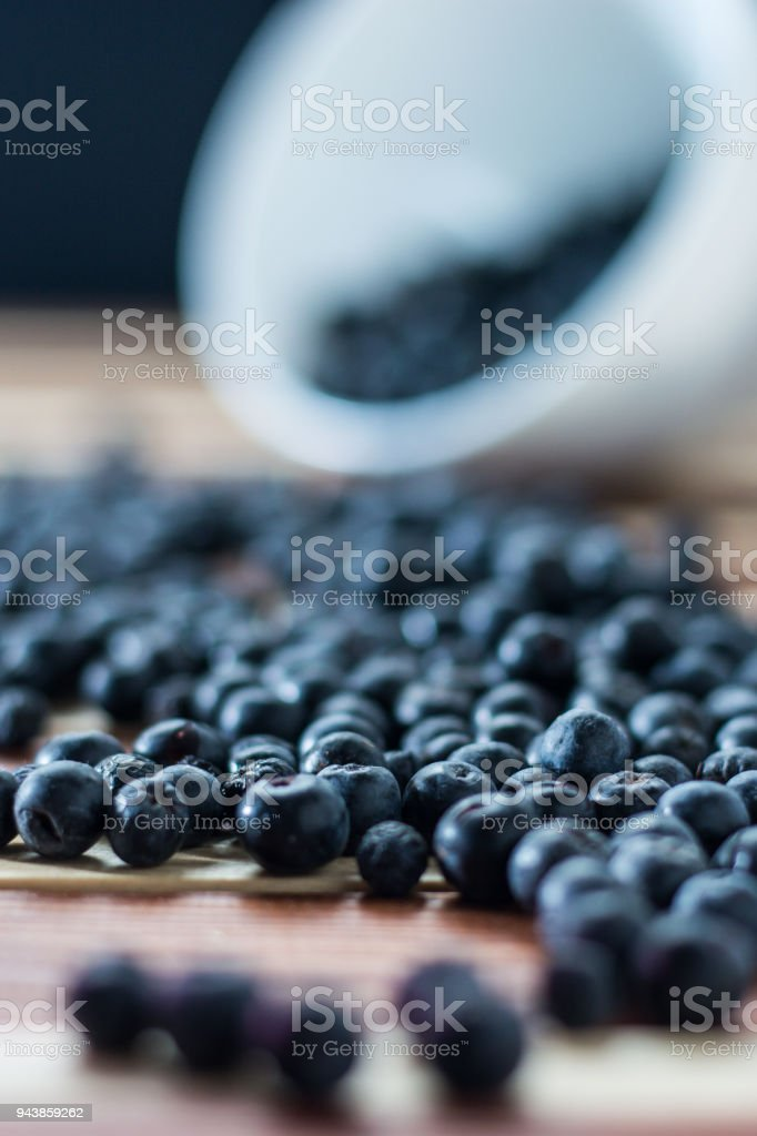 Bowl full of aronia spilled on wooden table stock photo
