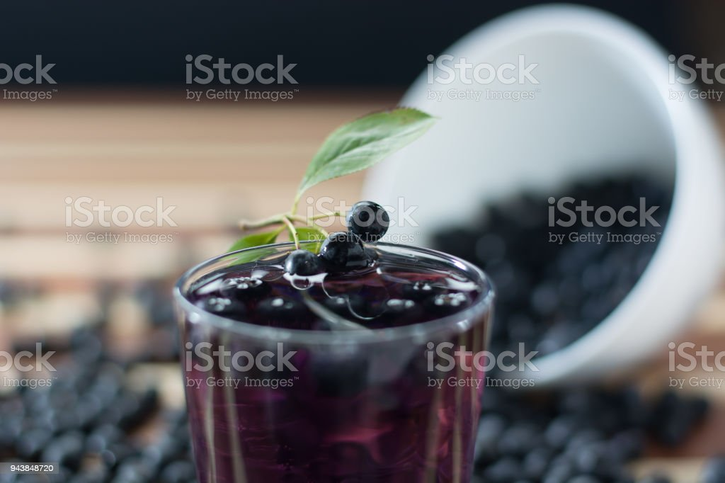 Bowl full of aronia with glass of aronia juice stock photo