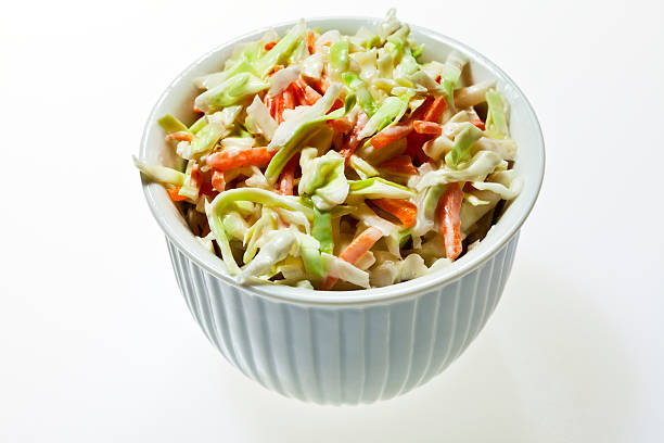 a bowl full of coleslaw on a white background - coleslaw stock pictures, royalty-free photos & images