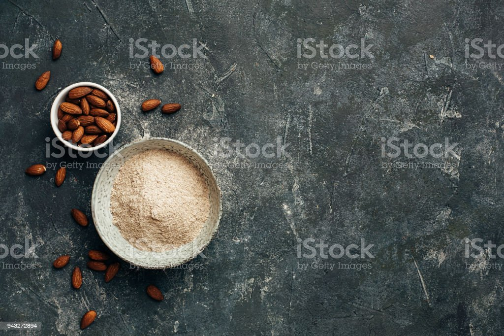 Bowl of almond flour and bowl of almonds from top view, copy space. stock photo