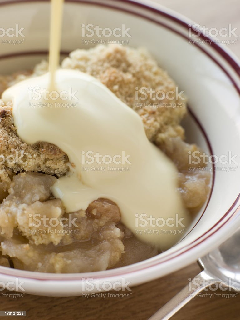 Bowl of Apple Crumble with Custard stock photo