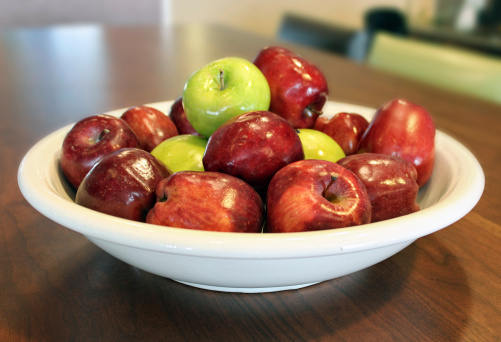 Bowl of Apples on Shiny Wood Table