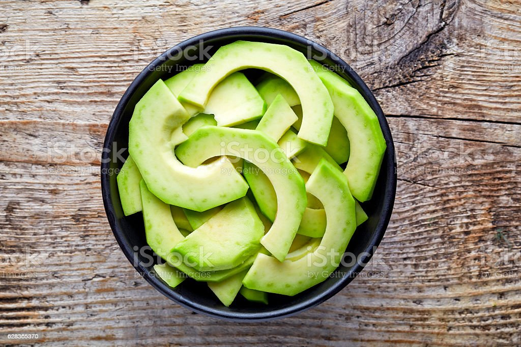 Bowl of avocado slices on wooden table, from above stock photo