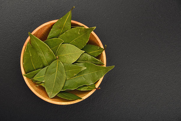 Bowl of bay leaves on black chalkboard stock photo