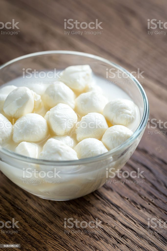 Bowl of Bocconcini mozzarella on the wooden table stock photo