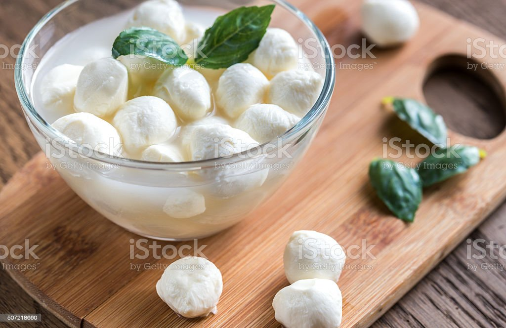 Bowl of Bocconcini mozzarella with fresh basil stock photo