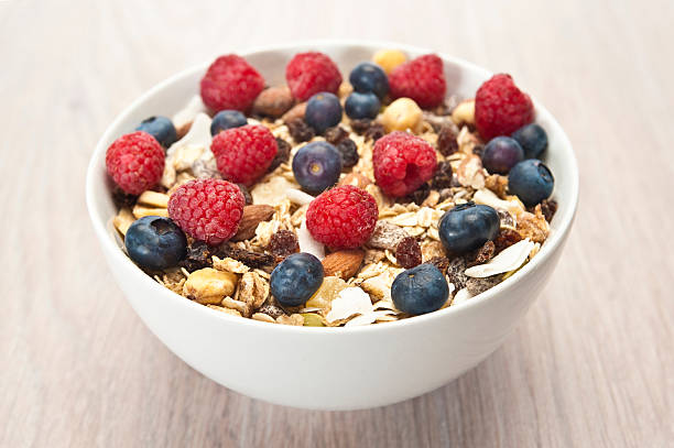 A bowl of breakfast cereals with blueberries and nuts