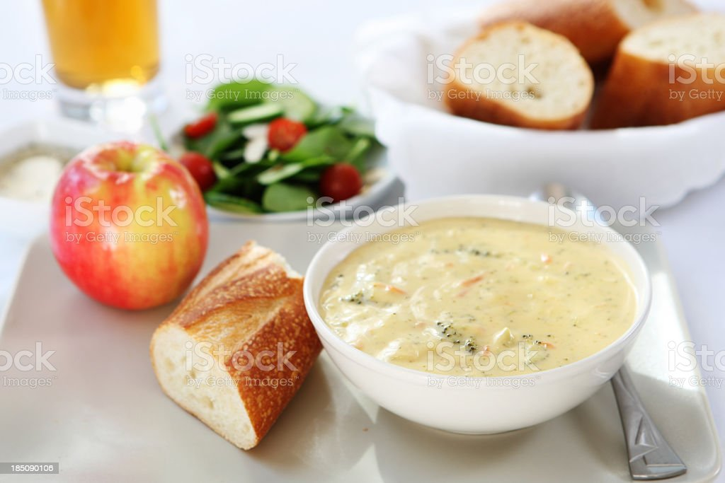 A bowl of broccoli cheddar soup, paired with bread and apple stock photo
