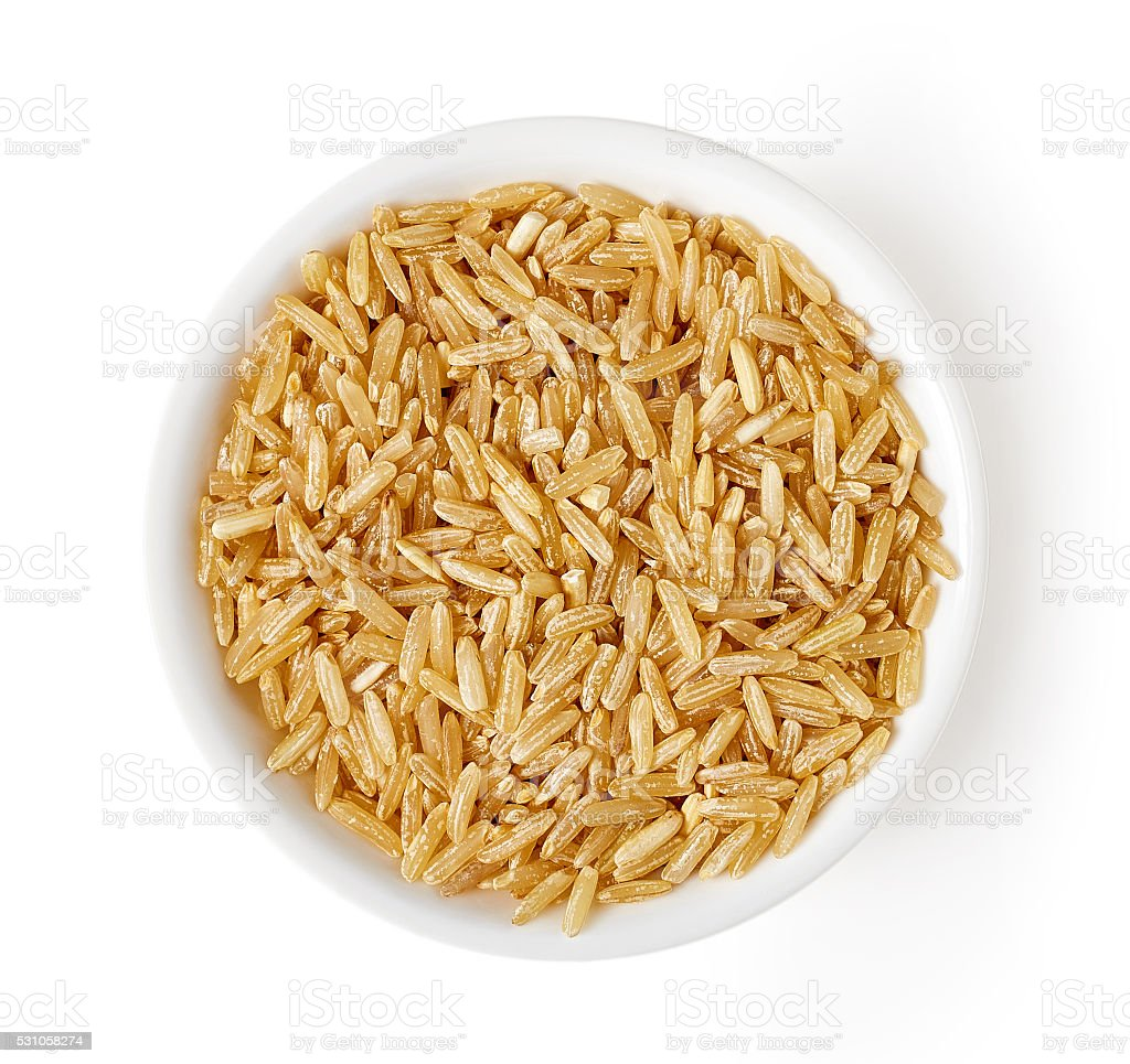 Bowl of brown rice isolated on white, from above stock photo