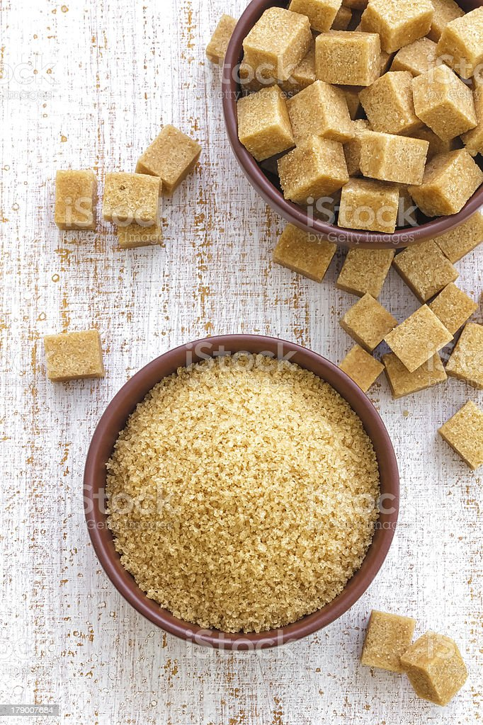 A bowl of brown sugar with sugar cubes on the side stock photo
