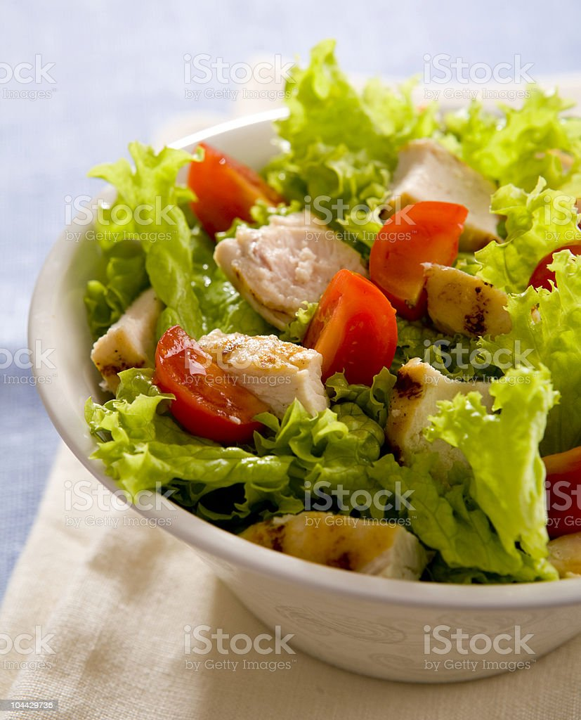 Bowl of Caesar salad showing chicken, tomato and lettuce royalty-free stock photo