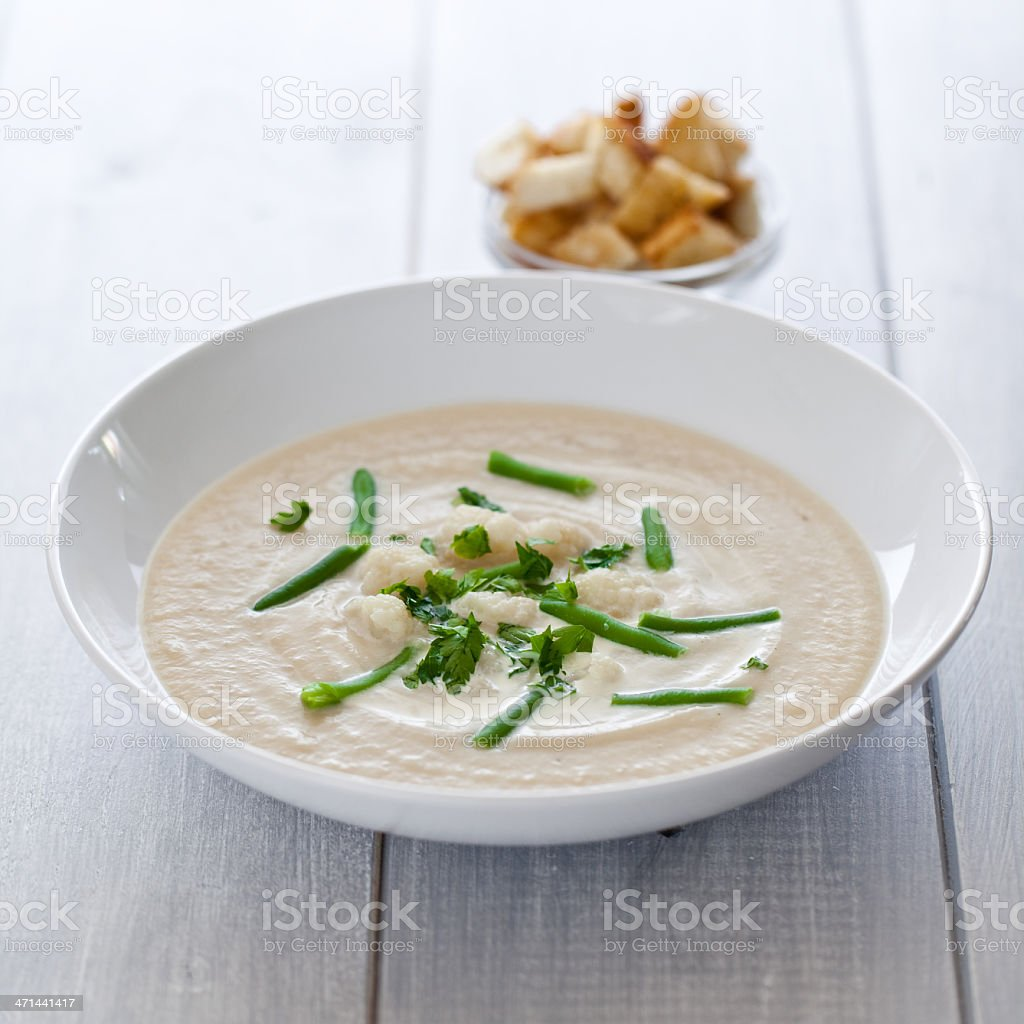 Bowl of cauliflower soup with greens on top royalty-free stock photo