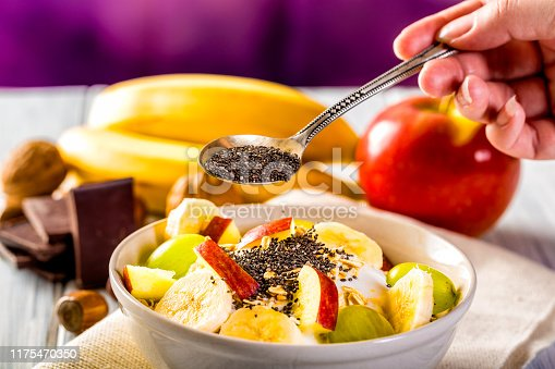 Healthy breakfast with yogurt, apple, banana and chia seeds. Bowl of fresh fruit.