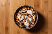 Bowl of bran cereal on a wood background
