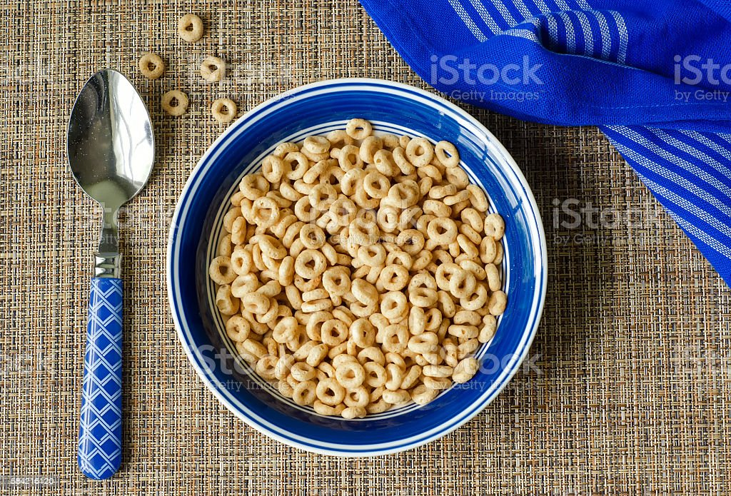 Bowl of cereal with spoon and blue napkin stock photo