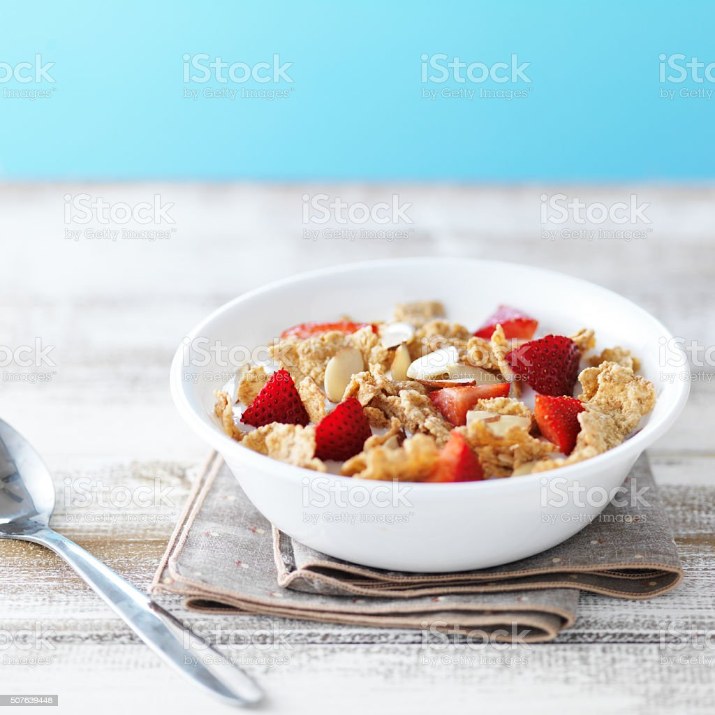 bowl of cereal with strawberries and almonds stock photo