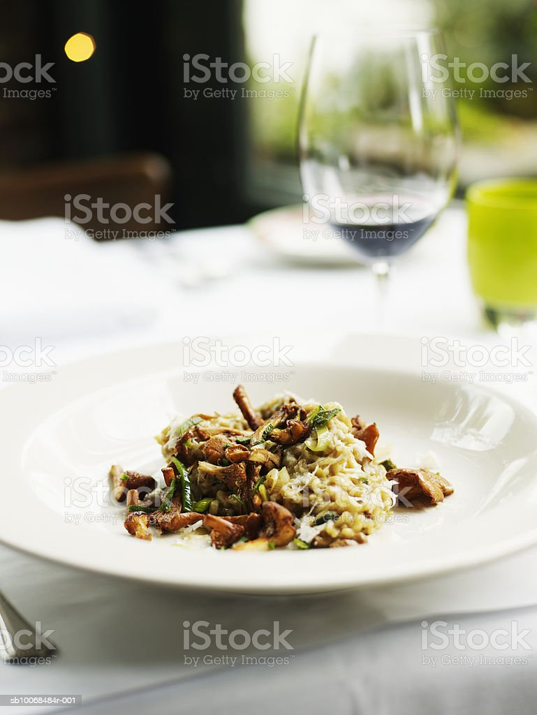 Bowl of chanterell mushroom risotto, wine glass in background, close-up foto de stock libre de derechos
