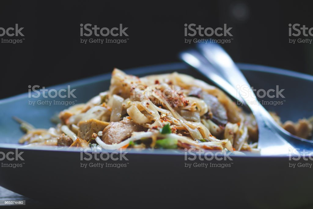Bowl of chicken chow mein sprinkled with red pepper flakes zbiór zdjęć royalty-free
