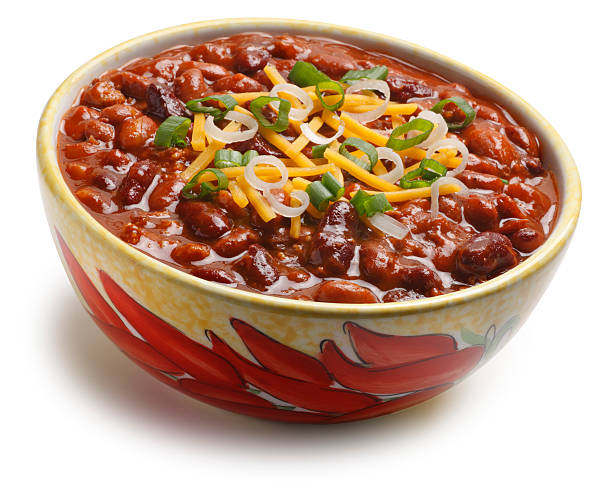Bowl of Chili Beans Isolated On White Background A bowl of chili beans in a bowl decorated with red chili peppers isolated on a white background.   The chili beans are topped with green onions shredded cheese.  Camera is tilted slightly off axis. A clipping path is included. chili con carne stock pictures, royalty-free photos & images