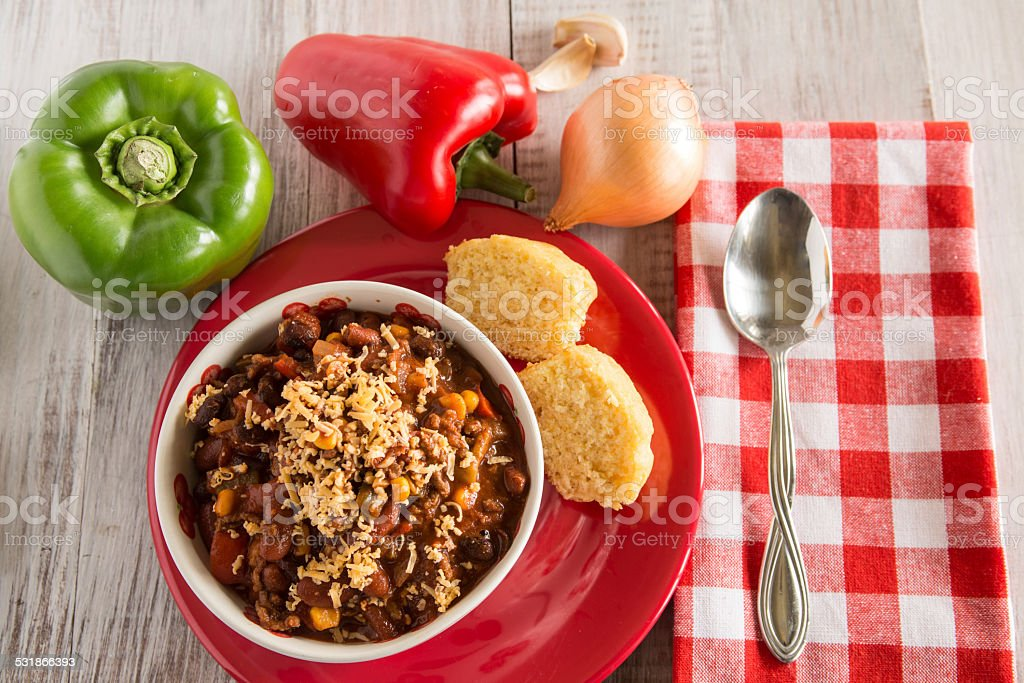 Bowl of Chili With Corn Bread Muffin And Vegetables Above stock photo