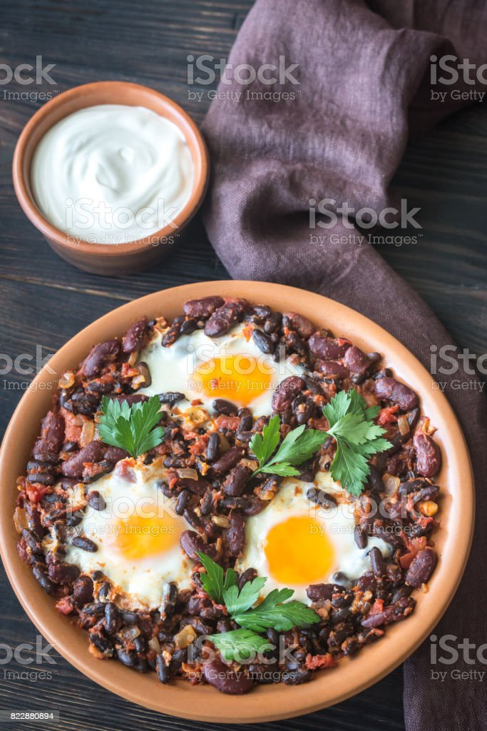 Bowl of chipotle bean chili with baked eggs stock photo