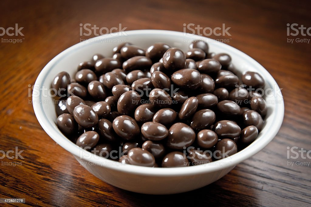 Bowl of chocolate coated raisins stock photo