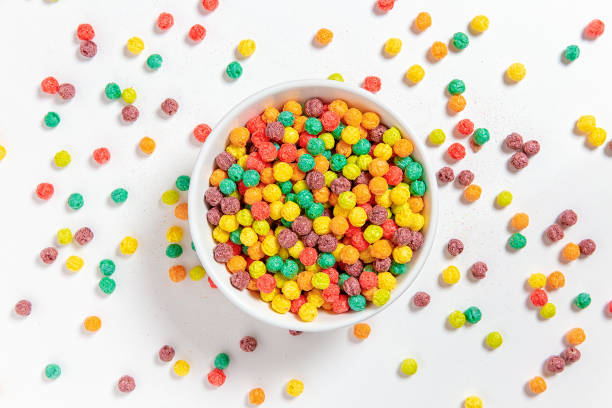 bowl of colorful cereal balls on white background stock photo