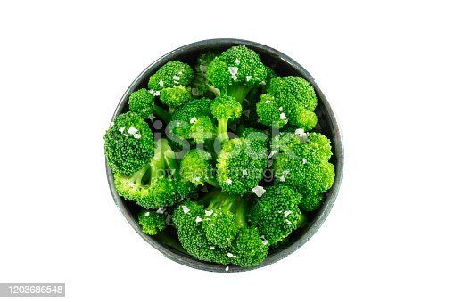 A bowl of cooked broccoli, isolated on a white background with a clipping path, shot from above with salt