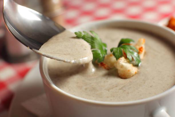 creme suppe mit champignon pilzen auf tisch - schnelle suppen stock-fotos und bilder