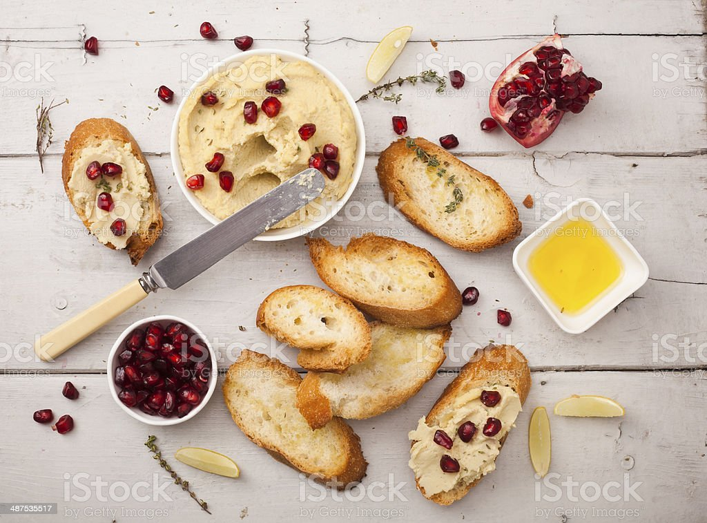 Bowl of creamy hummus with olive oil pomegranate and herbs stock photo