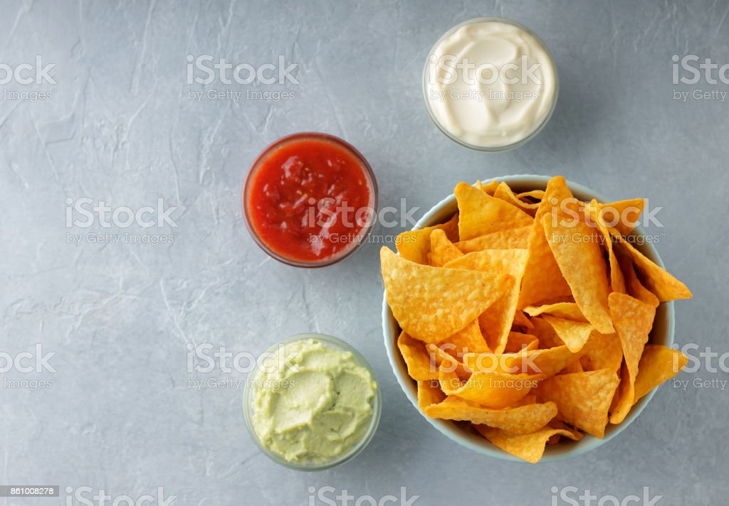 Bowl of crusty nachos or tortilla with different dipping sauces on gray stone background. stock photo