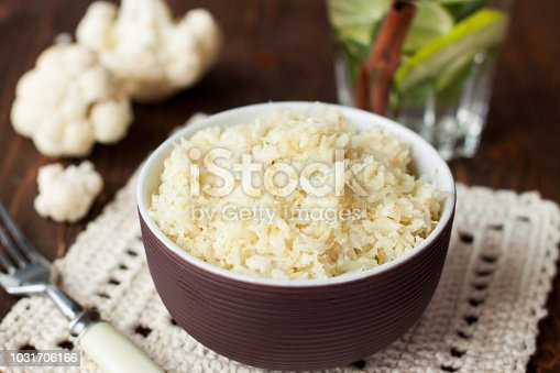 Bowl of diet paleo cauliflower rice on rustic wooden table