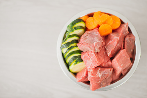 A photo of a bowl of dog food consisting of raw meat, carrots and cucumbers.