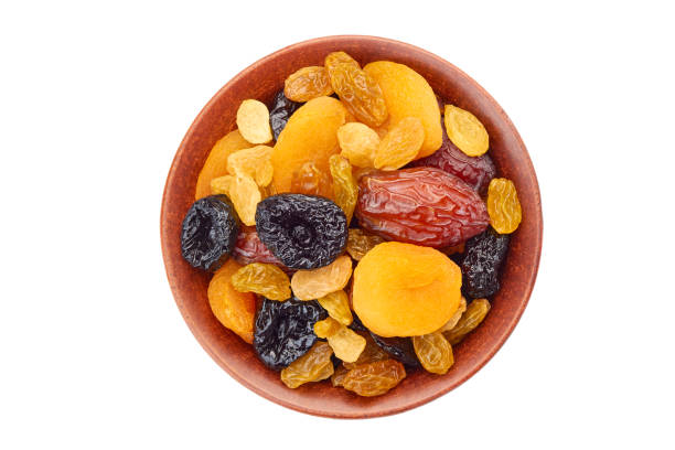 bowl of dried fruits mix on white - dried fruit stock photos and pictures